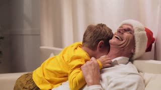 Joyful aged man resting with his grandson at home
