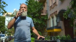 Joyful man smoking while promenading with bicycle