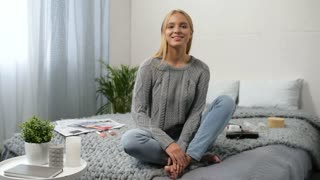 Like my video. Positive nice female blogger sitting in her bedroom while recording a video