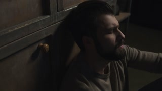 Loneliness. Close up of bearded man feeling lonely while sitting on the floor and drinking alcohol