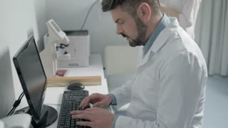 Male doctor working on computer in office