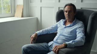 Middle aged man resting in the armchair