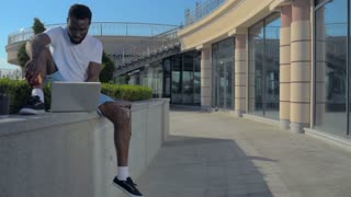 Millennial African American man lunching and working outdoors