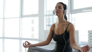 Mind peace. Close up of adorable young woman sitting in yoga position while listening to music and doing meditation