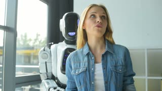 Mindful young lady showing robot its workplace