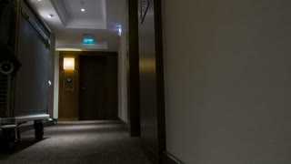 Moving along hotel feeble lighted hallway