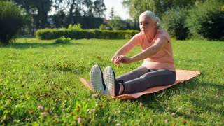 Nice aged woman doing sport exercises in the park