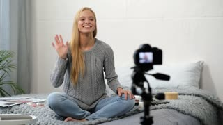 Nice colour. Smiling young woman recording a video for her beauty blog while using her lip gloss