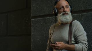 Pensive older man with headphones walking down street