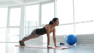 Perfect body shape. Full length of enthusiastic young woman doing push ups while being concentrated