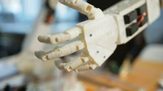Perfect construction. Close up of robots hand being repaired by experienced engineer using specific tools