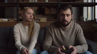 Player. Young angry girl pushing her husband while her husband playing video games and resisting her efforts for disturbing