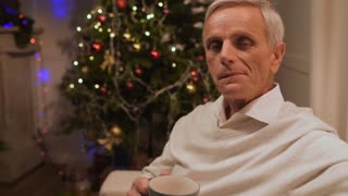 Pleasant aged man eating cookies at home