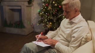 Pleasant aged man signing a christmas card