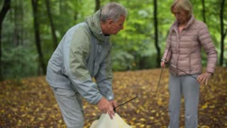 Pleasant eldelry woman helping her husband to set up the tent