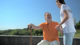 Pleasant female volunteer helping senior man