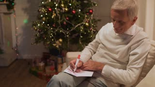 Pleasant retired man signing a Christmas card