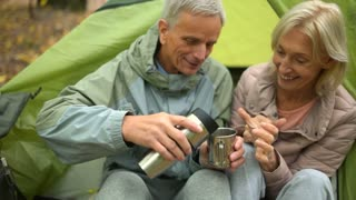 Pleasant senior man pouring tea for his wife