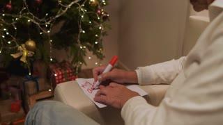 Pleasant senior man signing a Christmas card