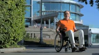 Pleasant senior man sitting in the wheelchair outdoors