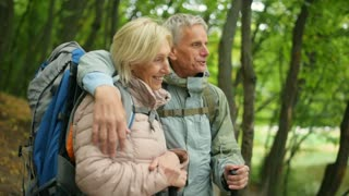 Positive aged couple enjoying active tourism in the forest