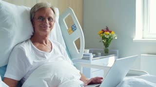 Positive aged man lying in the hospital bed with laptop