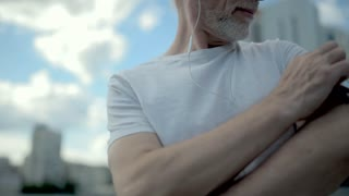 Positive aged man using his armband to choose right song