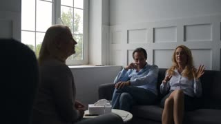 Positive couple sharing emotions with psychologist