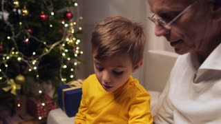 Positive elderly man signing Christmas cards with his grandson