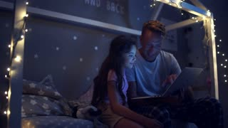 Positive little girl surfing the internet with her father