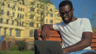 Positive man surfing internet outdoors and smiling into camera