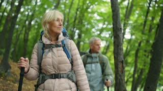 Positive retired woman walking with her husband in the wood
