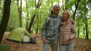 Positive senior couple walking in the forest