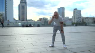 Positive senior man enjoying jogging in the city