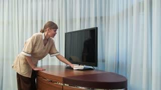 Positive smiling maid dusting TV set