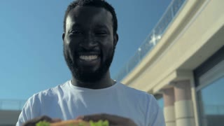 Radiant African American guy eating burger and looking into camera