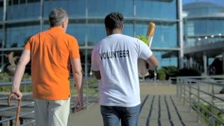 Rear view of an active volunteer helping a senior man