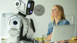 Robotic machine and woman looking at laptop and chatting