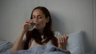 Sad adult woman drinking water in bed