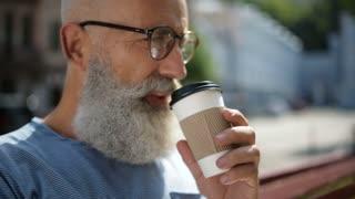 Senior gentleman wearing glasses drinking coffee outdoors