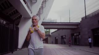Senior man jogging with dumbbells.