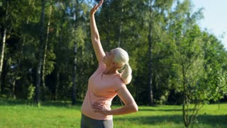 Senior nice woman doing warm up exercises outdoors