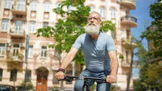 Serious grey haired man riding bicycle in city