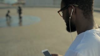 Side view on African American guy listening to music outdoors