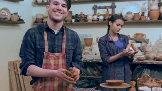 Smiling male potter shaping clay ball