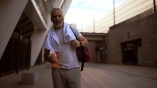Smiling senior man walking after sport exercises