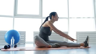 Sportive life. Full length of young adorable woman doing stretching exercises on the floor while being relaxed and positive