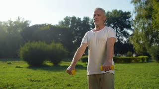 Sporty senior man exercising with the dumbbells in the park