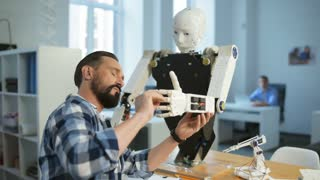 Talented and diligent. Close up of experienced engineer being attentive while standing and working on robot construction