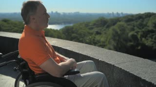 Thoughtful wheelchaired man enjoying the city view